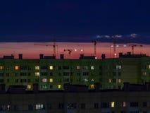 圣彼德堡,俄罗斯- 2018年7月24日:在五颜六色的日落天空背景的几台建筑用起重机  图库摄影