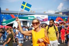 圣彼德堡,俄罗斯- 2018年6月18日:微笑和保留旗子的瑞典妇女 库存照片