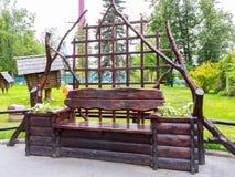 圣彼德堡,俄罗斯- 2018年7月10日:长木凳由与后面的日志做成在城市公园 免版税库存照片