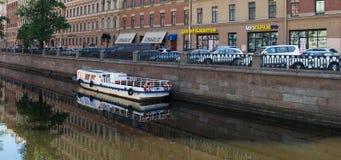 圣彼德堡,俄罗斯- 2016年6月01日:一艘小游船在其中一条圣彼德堡的运河中 免版税库存图片