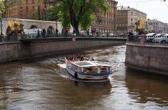 圣彼德堡,俄罗斯- 2016年5月14日:在Griboyedov运河的游船 船风帆在银行业务桥梁下 库存照片