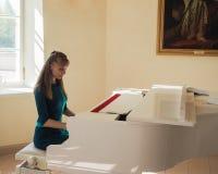圣彼德堡 使用在一架白色大平台钢琴的女性音乐家 免版税库存图片