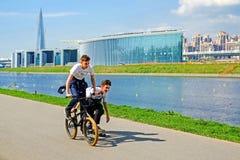 圣彼德堡 俄国 05 18 2018年 两个男孩乘坐自行车和滑板 库存图片