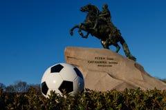 圣彼德堡 俄罗斯, 2018年5月9日:世界杯的概念在俄罗斯 以一个黄铜车手为背景的一个足球 M 库存照片