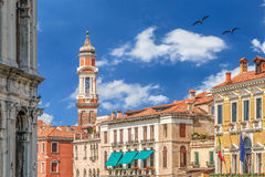 圣徒传道者与老时钟的钟楼在有五颜六色的蓝天和白色云彩的威尼斯-意大利 库存照片