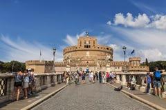 圣徒天使桥梁的游人横跨俯视圣徒天使城堡或艾德里安娜,罗马的陵墓台伯河 免版税库存照片