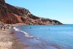圣托里尼,希腊- 2018年7月21日:红色海滩的沐浴者在圣托里尼,希腊,欧洲火山岛  库存图片