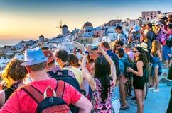 圣托里尼,希腊- 2014年7月12日:游人在Oia享受日落 免版税图库摄影
