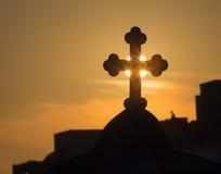 圣托里尼-十字架的剪影在典型地教会圆屋顶的在日落的Oia 免版税图库摄影
