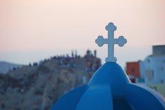 圣托里尼-在典型教会的十字架在Oia和在堡垒废墟的人剪影 库存照片