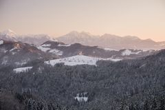 圣托马斯教会美好的日出风景在小山顶的斯洛文尼亚在冬天和特里格拉夫峰山背景中 免版税库存照片