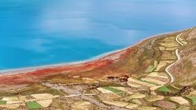 圣洁羊卓雍错和五颜六色的农场土地,与小的波纹的令人惊讶的大海表面大角度看法  免版税图库摄影