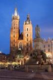 圣玛丽大教堂和亚当・密茨凯维奇纪念碑在晚上在克拉科夫 库存照片