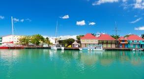 圣约翰斯,安提瓜岛- 2016年3月05日:与房子和游艇的码头在蓝天的绿松石海 旅行和旅行癖 图库摄影
