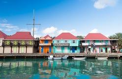 圣约翰斯,安提瓜岛- 2016年3月05日:小船在海靠了码头在与房子的村庄码头蓝天的 暑假 免版税库存照片
