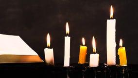 圣经和蜡烛在一张老木被烧的桌上 美好的黑暗的背景 影视素材
