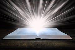 圣经谎言的大书在一张木桌上的 在黑暗 光在书从上面发光 光从书出来 图库摄影