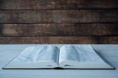 圣经谎言的大书在一张木桌上的 在黑暗 光在书从上面发光 库存图片