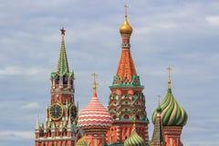 圣蓬蒿红场的` s大教堂葱圆顶反对克里姆林宫Spasskaya塔剧烈的多云s背景的  免版税库存图片