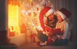 圣诞前夕礼品节假日许多装饰品 家庭母亲和儿童女儿读书魔术bo 图库摄影