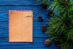 圣诞前夕设置了与云杉的分支、杉木锥体和笔记本决议的对蓝色木背景上面veiw嘲笑 免版税库存照片