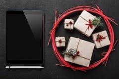 圣诞卡、技术和礼物技术恋人的, iPad地方消息的亲人的在新年礼物外面 免版税库存照片