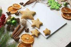 圣诞卡片、一张空白的圣诞节球围拢的纸片和姜饼,冷杉分支,肉桂条,香料,干 免版税图库摄影