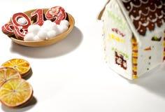 圣诞卡片:在一块木板材上是红姜曲奇饼以第的形式2019年和白色圆的雪花 图库摄影