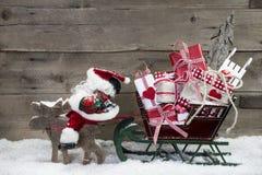 圣诞卡装饰:拉扯礼物的圣诞老人雪橇麋 图库摄影