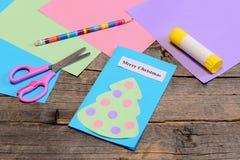 圣诞卡讲解 与文本圣诞快乐,铅笔,胶浆棍子的纸贺卡,色纸覆盖,剪 免版税库存照片