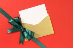 圣诞卡,红色礼物纸背景,对角绿色丝带的弓,白色拷贝空间 免版税库存照片