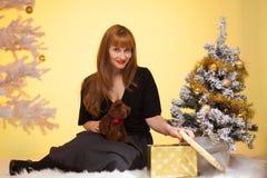 圣诞卡:在圣诞树附近的一个美丽的女孩打开礼物 免版税库存照片