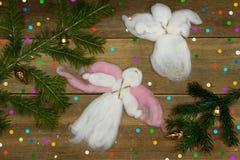 圣诞卡:飞行两个白色羊毛的天使,五颜六色的五彩纸屑和分支在木板条 免版税库存照片