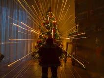 圣诞夜在有玩偶圣诞老人和作用温暖的光烟花的房子里 免版税库存照片
