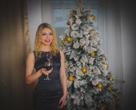 圣诞夜,一件黑礼服的一个美丽的女孩有一杯的酒 免版税图库摄影