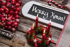 圣诞快乐与四个燃烧的红色蜡烛的贺卡 免版税库存图片