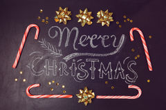 圣诞快乐与黑板字法和棒棒糖的贺卡设计 在视图之上 免版税库存照片