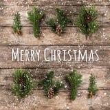 圣诞快乐印刷在与冷杉分支、杉木锥体和雪花的木背景在木背景 Xmas和新 免版税库存照片