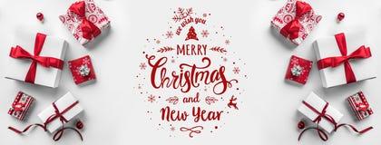 圣诞快乐印刷在与礼物盒和红色装饰的白色背景 免版税库存图片