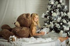 圣诞快乐和愉快的假日 相当有长的头发的白肤金发的女孩拿着大玩具熊 免版税库存图片