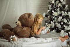 圣诞快乐和愉快的假日 相当有长的头发的白肤金发的女孩拿着大玩具熊 免版税图库摄影