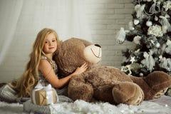 圣诞快乐和愉快的假日 相当有长的头发的白肤金发的女孩拿着大玩具熊 库存图片