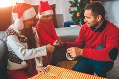 圣诞快乐和新年好 一起准备礼物的家庭的好的图片 女孩和年轻人举行磁带 免版税图库摄影