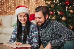 圣诞快乐和新年好 在家庆祝假日的年轻夫妇 男人和妇女读一本书 免版税库存照片