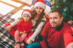 圣诞快乐和新年好 好家庭的图片 年轻人举行照相机和作为selfie 所有摆在 免版税库存照片