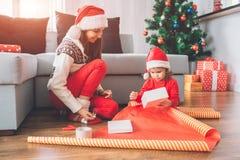 圣诞快乐和新年好 小女孩坐地板 她在手上拿着白色箱子 孩子设法包装它 免版税图库摄影