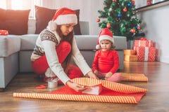 圣诞快乐和新年好 Seriousand集中了妇女用纸坐并且盖箱子 小女孩看 免版税库存照片
