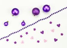 圣诞快乐和新年快乐构成和装饰:圣诞节玩具、花冠、桃红色紫心勋章和花 免版税库存照片