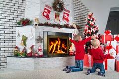 圣诞快乐和节日快乐!两个兄弟发现了许多礼物在圣诞树下 免版税库存图片
