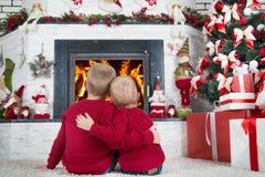 圣诞快乐和节日快乐!两个兄弟坐地板在客厅和神色在壁炉的火 在a 免版税库存照片